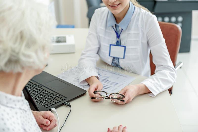 Le ögonläkaren som håller den nödvändiga eyewearen royaltyfri foto