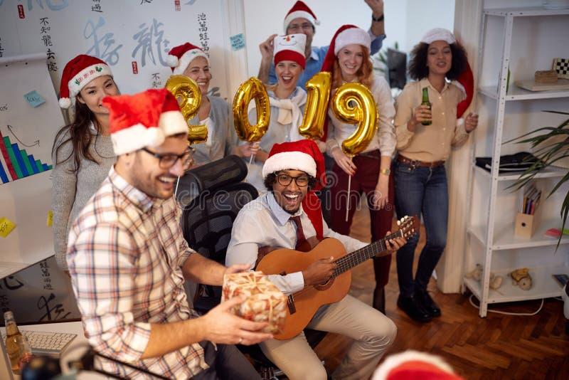 Le affär har arbetare gyckel i jultomtenhatt på julpartiet arkivbilder