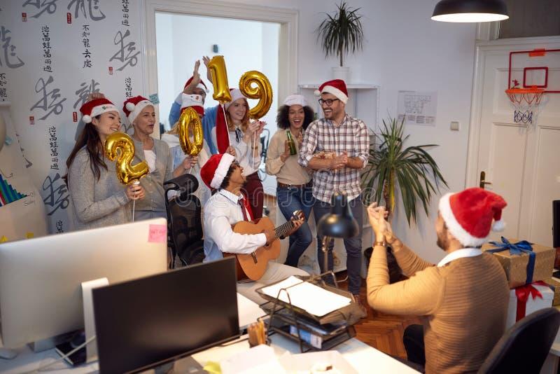 Le affär har arbetare gyckel och dans i jultomtenhatt på julpartiet royaltyfri foto
