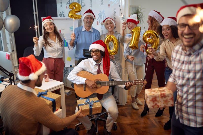 Le affär har folket gyckel och dans i jultomtenhatt på Xmas-parti- och utbytesgåvor arkivbilder