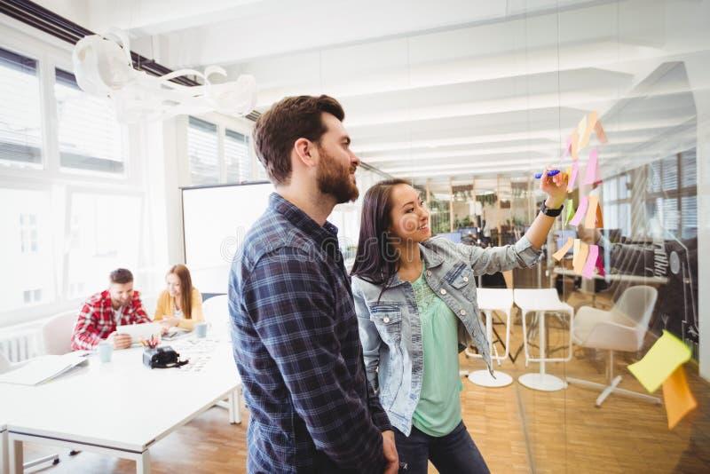 Le affärsfolk som ser mång- kulöra klibbiga anmärkningar på exponeringsglas arkivfoto