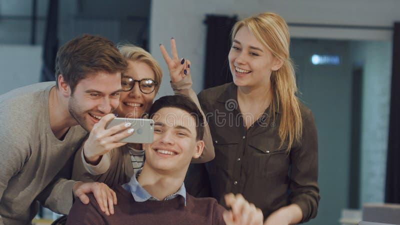 Le affärsfolk som tar selfie i mötesrum på det idérika kontoret arkivbild