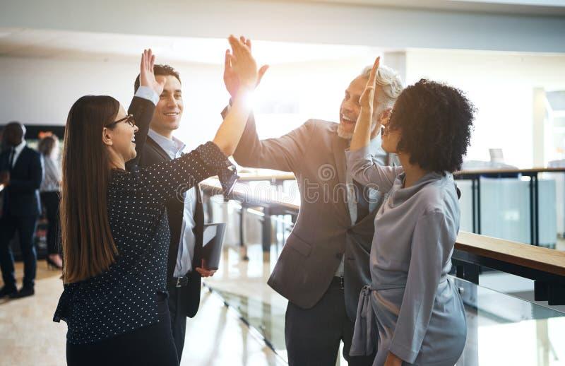 Le affärskollegor som fiving sig högt i ett kontor arkivfoton