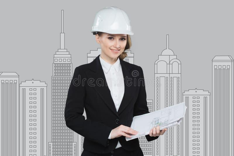 Le affärskvinnan i hjälm som studerar skissa av det framtida affärscentrumet arkivfoto