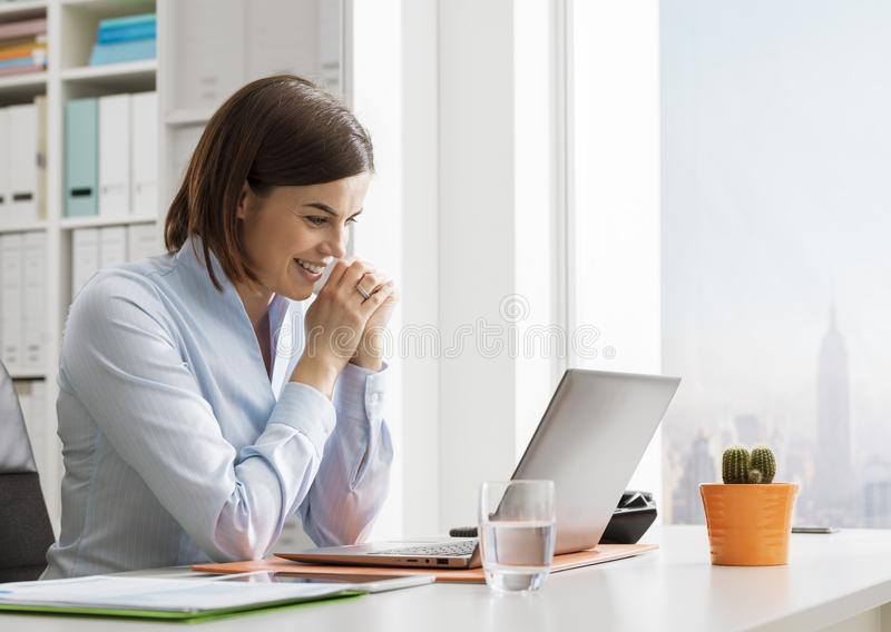 Le affärskvinnan som arbetar och förbinder med hennes bärbar dator royaltyfri fotografi