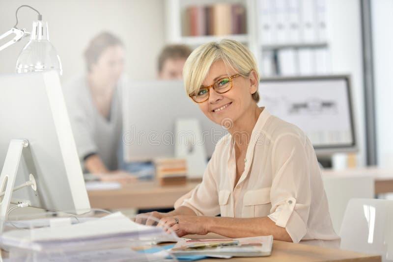 Le affärskvinnan som arbetar på den skrivbords- datoren royaltyfri foto