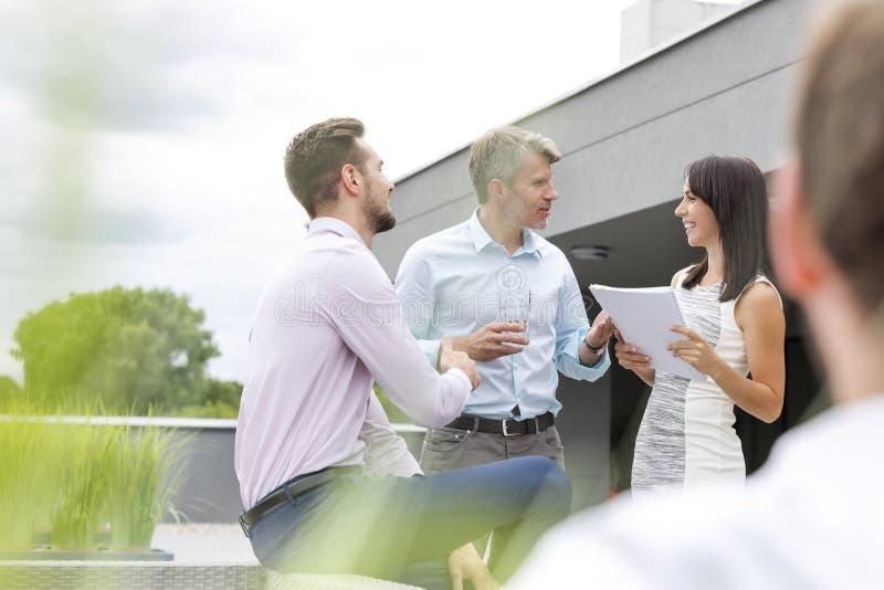 Le affärskvinnan som diskuterar över dokument med kollegor på kontorsterrassen royaltyfri bild