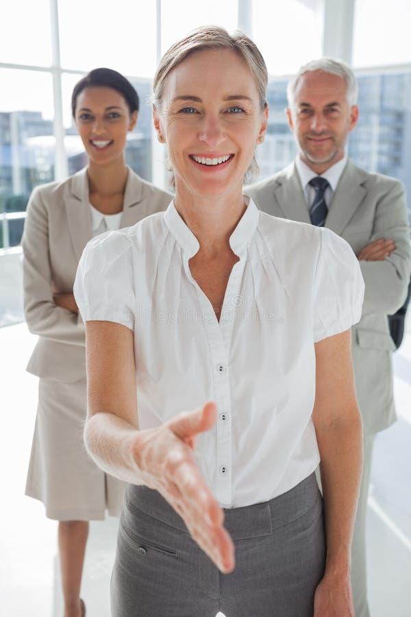 Le affärskvinnan som ger en handskakning med kollegor bakom royaltyfri fotografi