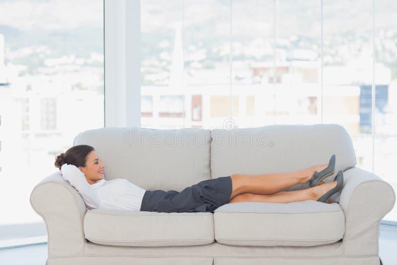 Le affärskvinnan som ner ligger på soffan royaltyfria bilder