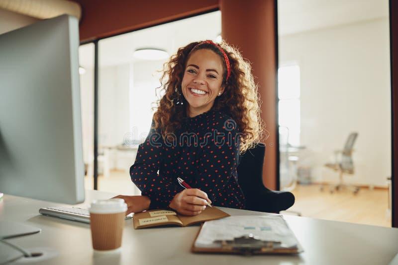 Le affärskvinnan som ner skriver anmärkningar, medan arbeta på hennes de fotografering för bildbyråer