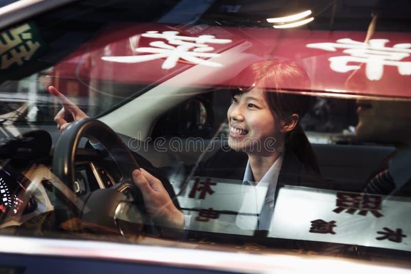 Le affärskvinnan som pekar ut ur bilen, medan köra till och med Peking på natten arkivbild