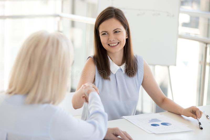 Le affärskvinnan som skakar handen av kollegan på företagsmötet arkivbilder