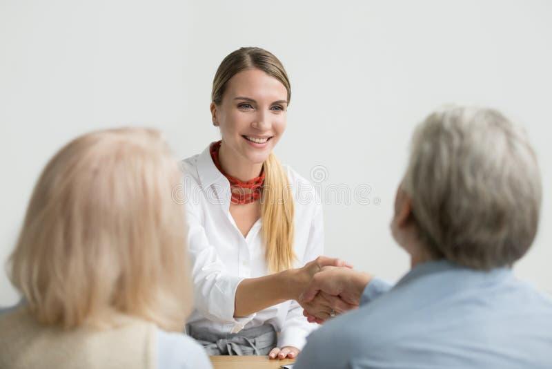 Le affärskvinnan som skakar handen av pensionären timme på jobbintervjun royaltyfri fotografi
