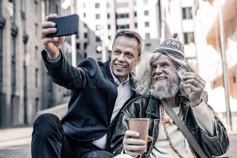 Le affärsmän i den mörka dräkten som gör selfie med lycklig hemlös arkivfoton