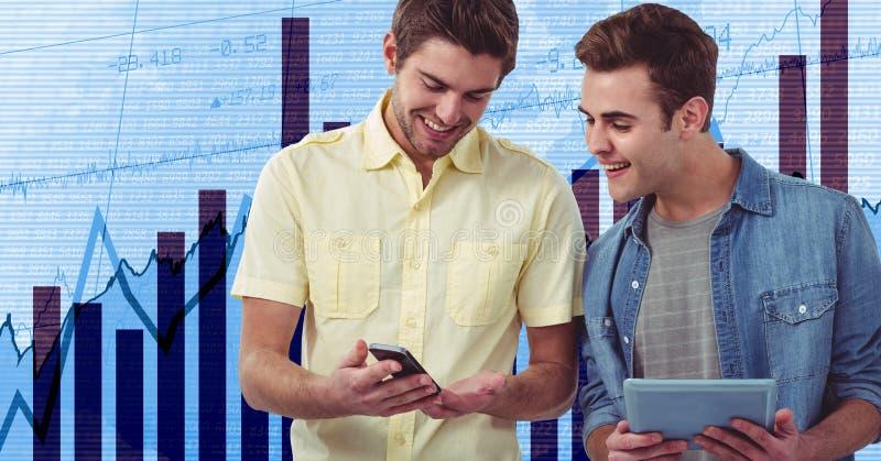 Le affärsmän som rymmer mobiltelefon- och minnestavlaPC mot grafer royaltyfri bild