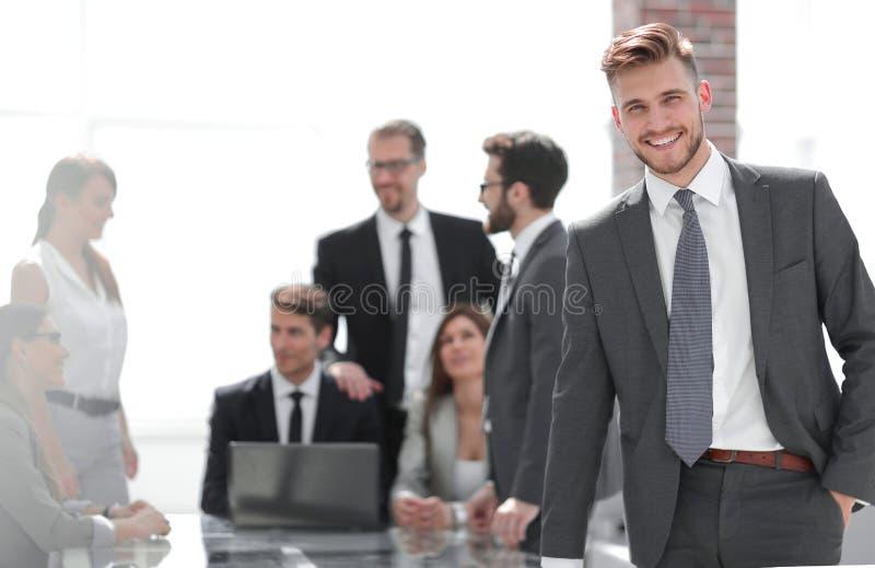 Le affärsmananseende nära skrivbordet royaltyfria foton