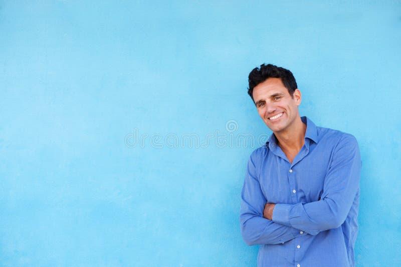 Le affärsmanbenägenhet mot den blåa väggen arkivbild