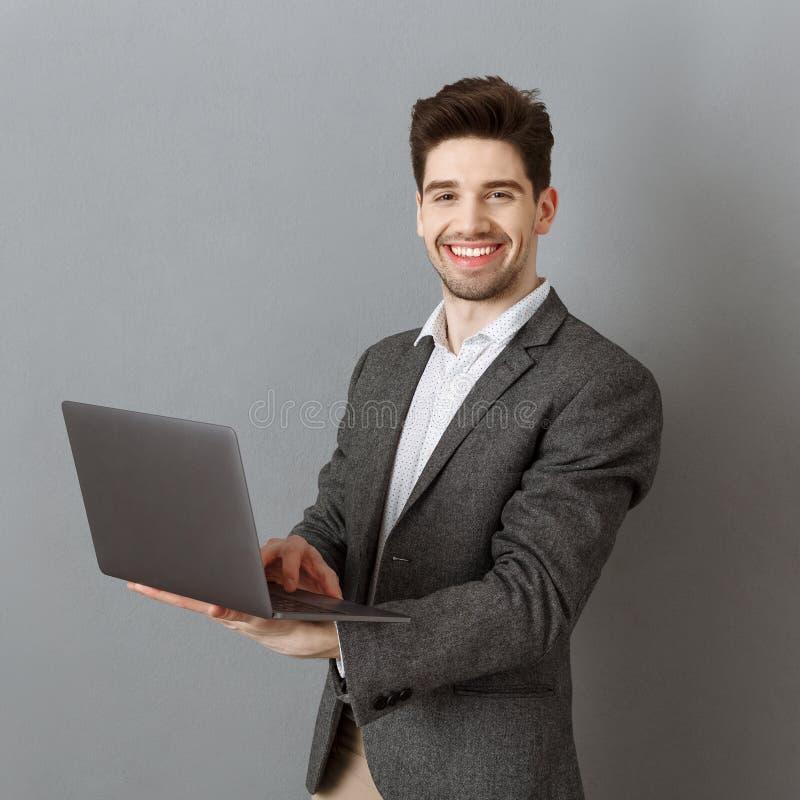 le affärsmannen i dräkt med bärbara datorn mot grå färger arkivfoton