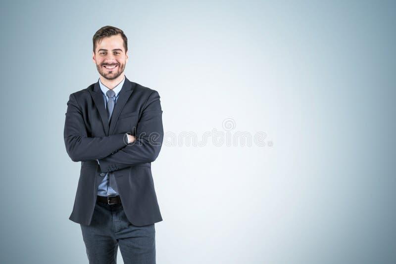 Le affärsmannen med korsade armar, grå vägg royaltyfria bilder