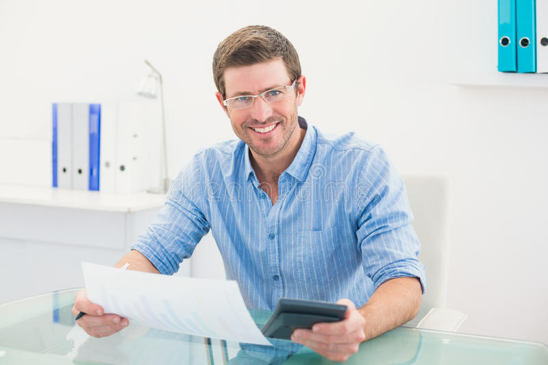 Le affärsmannen som arbetar på hans finanser på hans skrivbord royaltyfri foto