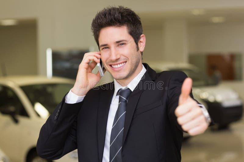 Le affärsmannen som ger tummar upp på telefonen arkivbilder