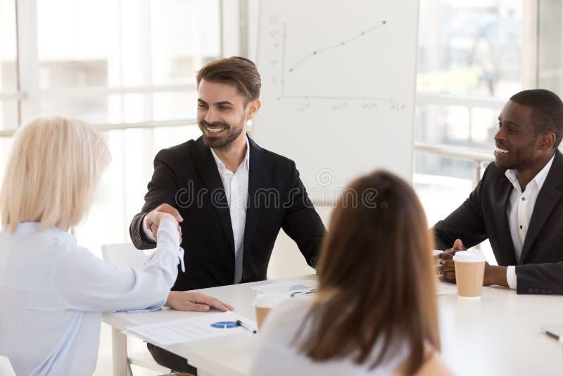 Le affärsmannen som skakar handen av den mogna kvinnan på möte royaltyfri foto
