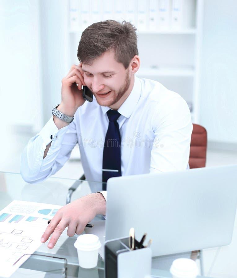 Le affärsmannen som talar på telefonsammanträdet på hans skrivbord fotografering för bildbyråer