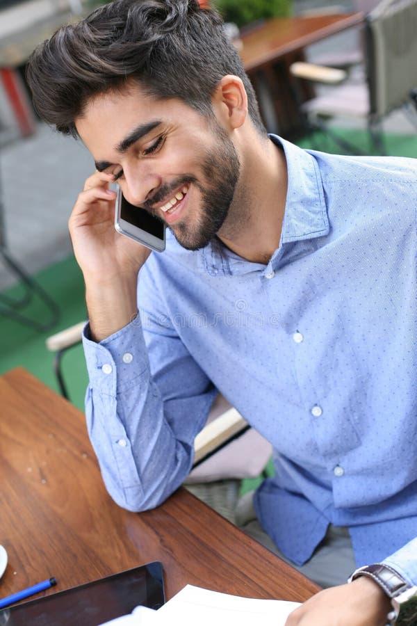 Le affärsmansammanträde i kafé och samtal på mobi royaltyfri fotografi