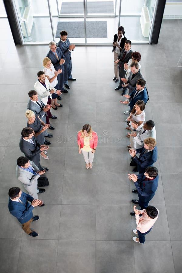 Le affärspartners som applåderar till den säkra ledaren royaltyfri bild