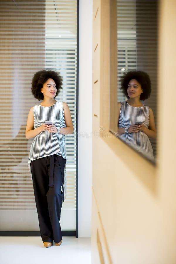 Le afrikansk amerikanaffärskvinnan som in använder mobiltelefonen av arkivfoton