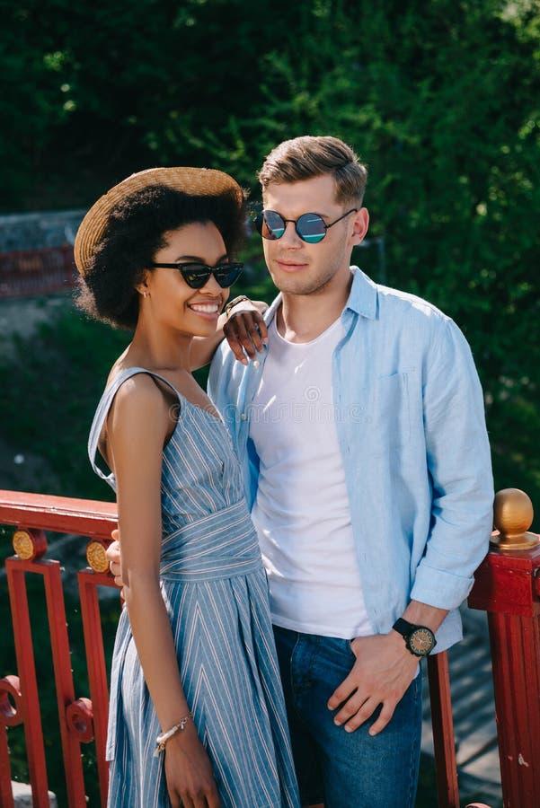 le afrikansk amerikankvinnan i solglasögon som står med pojkvännen fotografering för bildbyråer