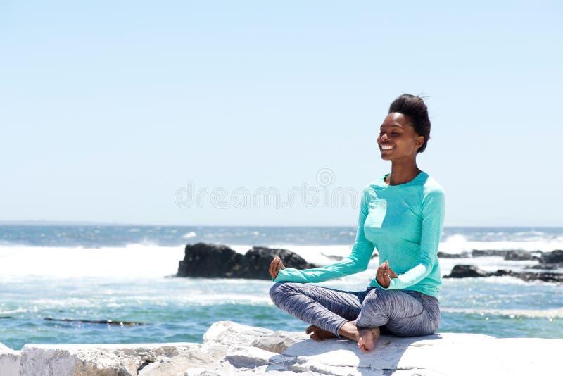 Le afrikansk amerikankvinnan som gör yoga vid havet royaltyfri foto
