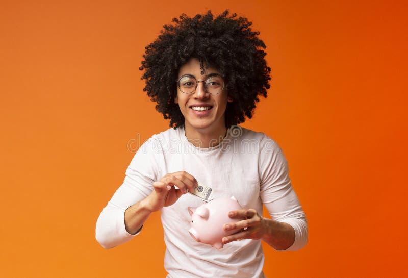 Le afrikansk amerikanmannen som sätter pengar i hans spargris fotografering för bildbyråer