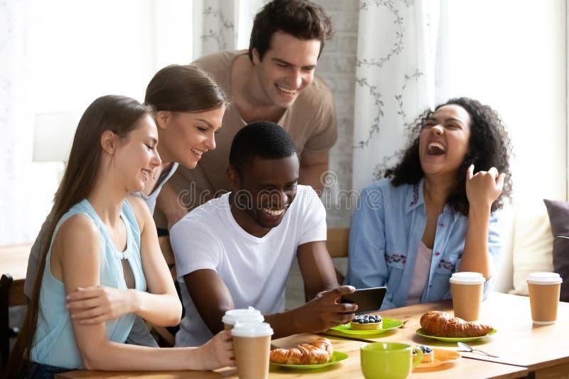 Le afrikansk amerikanmannen som visar den roliga videoen till vänner fotografering för bildbyråer