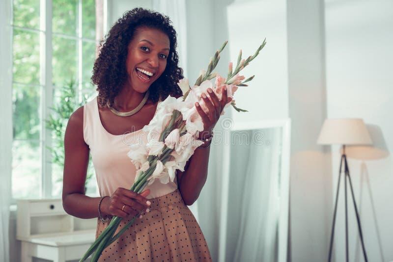 Le Afro--amerikanen som rymmer lyckligt härliga blommor av gladioluses royaltyfri fotografi