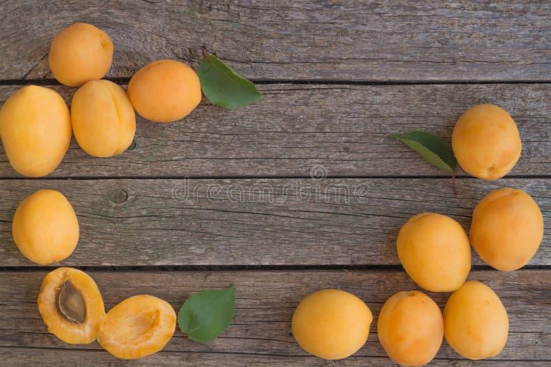 Le albicocche arancio mature sono sistemate sui left and right di fondo di legno fotografie stock