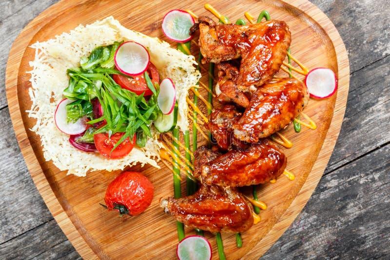 Le ali di pollo fritto con insalata fresca, le verdure arrostite ed il bbq sauce sul tagliere su fondo di legno immagini stock