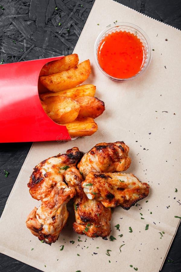 Le ali di pollo fritto con le patate al forno ed il bbq sauce sulla carta del mestiere su fondo nero fotografie stock libere da diritti