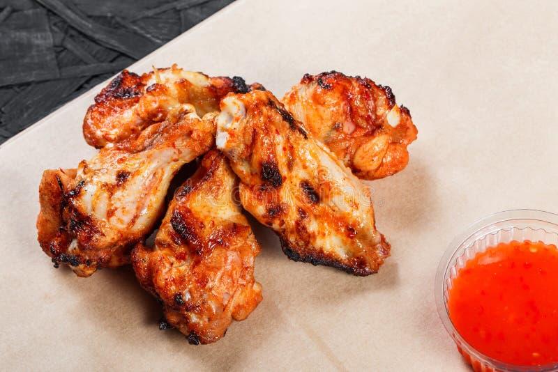 Le ali di pollo fritto con le patate al forno ed il bbq sauce sulla carta del mestiere su fondo nero Piatti caldi della carne fotografia stock