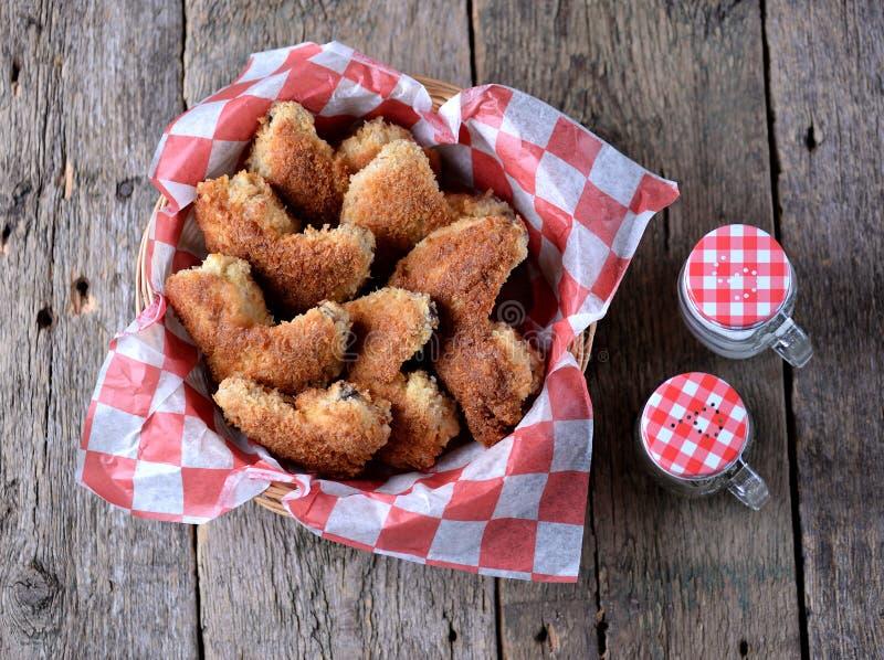 Le ali di pollo hanno fritto nell'impanare con la salsa al pomodoro, alimenti a rapida preparazione immagine stock