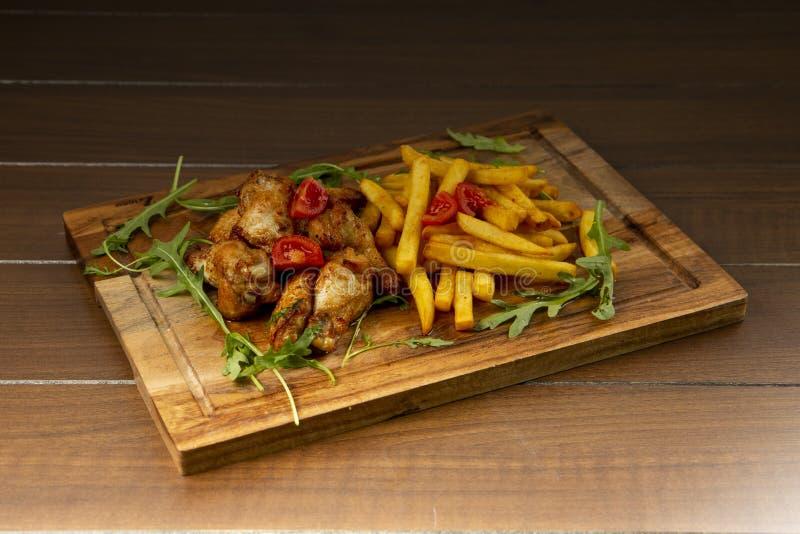 Le ali di pollo sono servito sul bordo di legno fotografie stock libere da diritti
