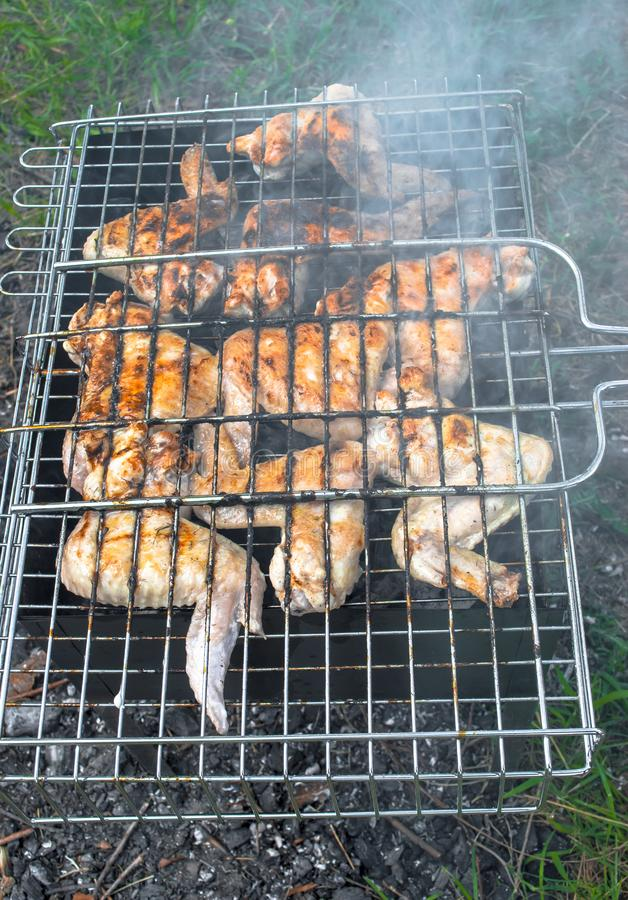 Le ali succose del BBQ sono fritte con fumo sulla griglia immagine stock libera da diritti
