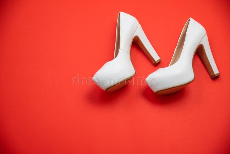 Le alte scarpe tallonate bianche, fondo rosso - concetto di vista superiore - tallona la sinistra di camminata immagine stock libera da diritti