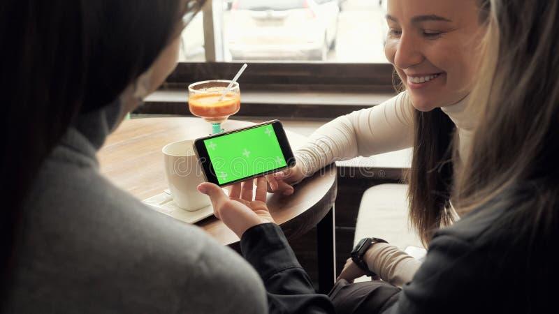 Le amiche delle donne stanno esaminando lo schermo verde in smartphone e stanno parlandolo che si siede in caffè fotografia stock