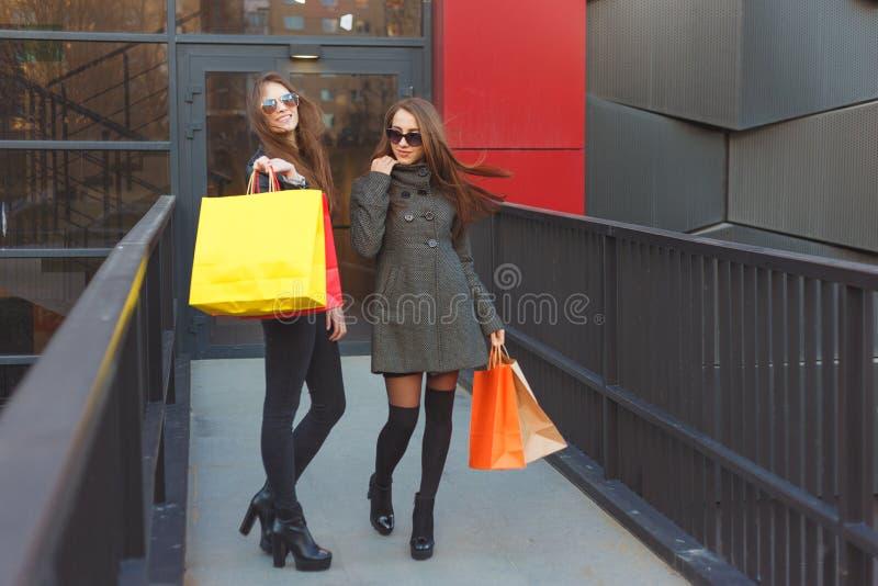 Le amiche delle giovani donne vanno con i pacchetti di colore in pieno di acquisto dal centro commerciale fotografia stock
