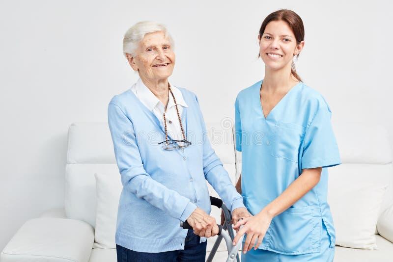 Le anhörigvårdaren med den lyckliga äldre kvinnan arkivfoton