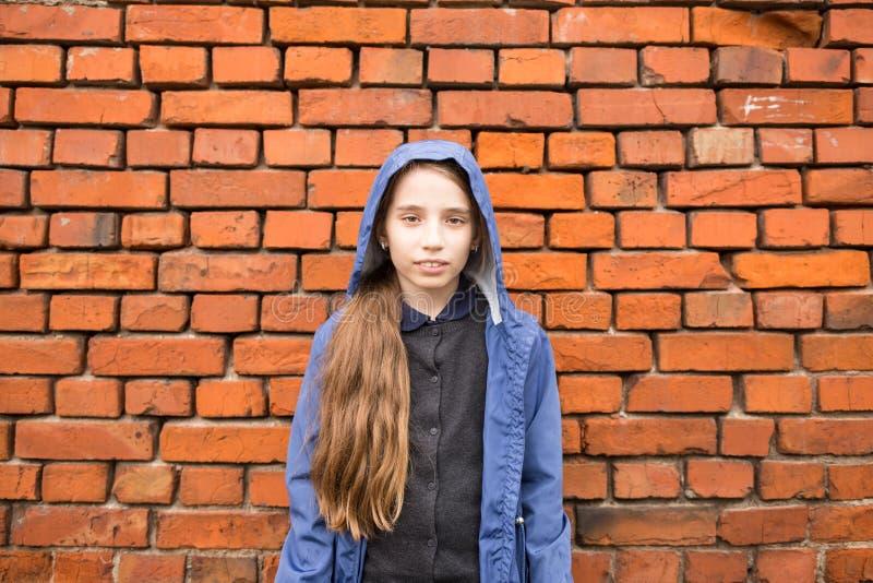 Le anseende för tonårs- flicka mot tegelstenväggen royaltyfri bild