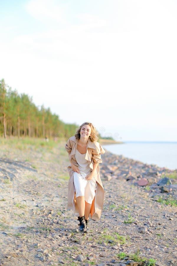 Le anseende för ung kvinna på havsstranden med träd i bakgrund arkivbild