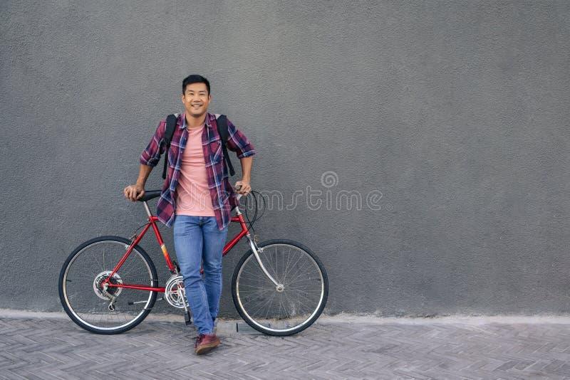 Le anseende för ung man med hans cykel mot en vägg fotografering för bildbyråer
