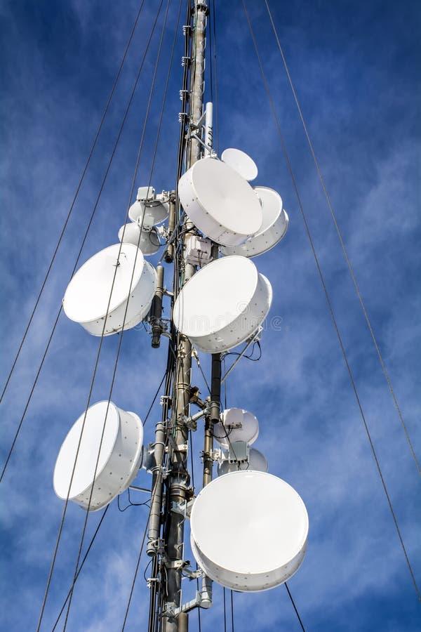 Le antenne sulla rete mobile si elevano su un cielo blu Sistema globale per le comunicazioni via radio immagine stock